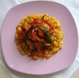 Pollo casareccio con verdure di stagione, adagiato su un letto di pattate fritte.